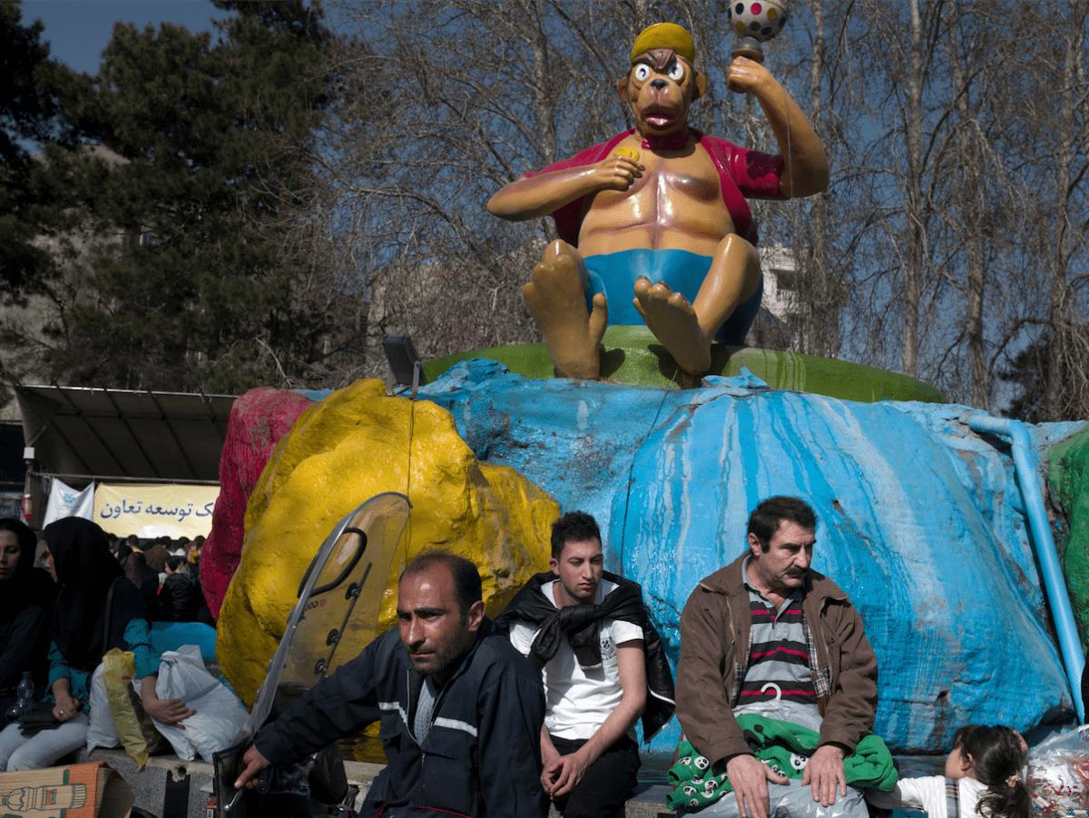 Trois hommes observent la foule au parc d'attractions Eram dans l'ouest de Téhéran. Pendant longtemps, ce parc était le seul lieu de loisirs à l'air libre de Téhéran, mais les années se font sentir : les lions ont vieilli et certaines des attractions sont fermées. © Newsha Tavakolian pour la Fondation Carmignac