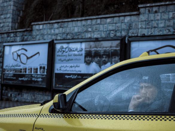 Chauffeur de taxi dans son véhicule un jour de pluie. Derrière lui, une affiche d'une prochaine représentation de la pièce de Samuel Beckett, En attendant Godot © Newsha Tavakolian pour la Fondation Carmignac