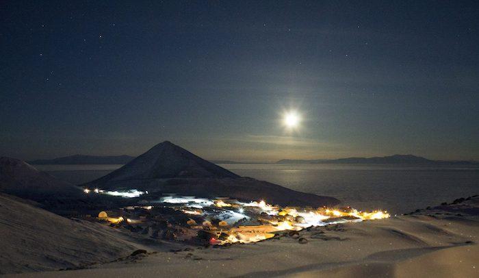 La lune brille au-dessus de la station McMurdo en juin, où la nuit dure 24 heures. La station McMurdo est l'un des lieux où les artistes séjournent durant leur résidence. © Andrew Smith / NSF