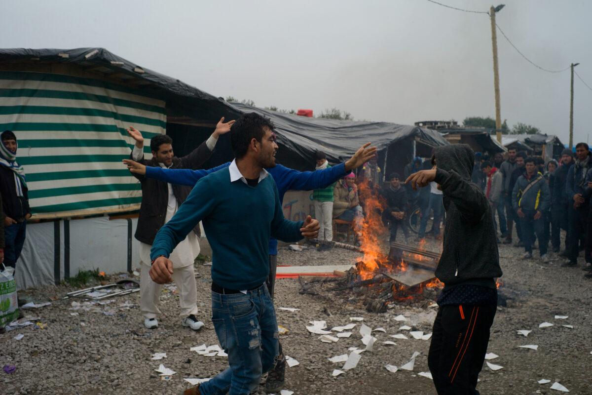 De jeunes afghans dansent autour d'un feu, la veille de l'opération d'évacuation du camp de réfugiés de Lande à Calais, le 23 octobre 2016 / © Rafael Yaghobzadeh