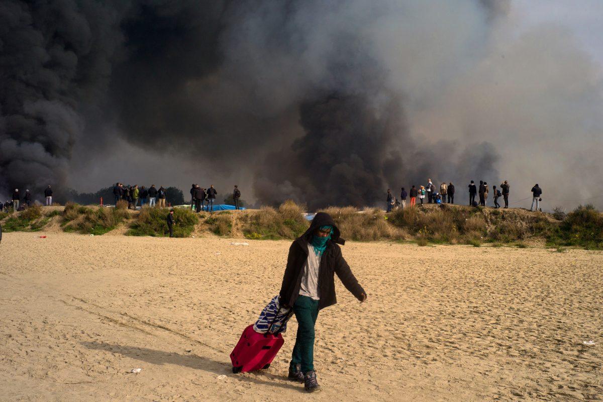 Un Soudanais munis de ses affaires personnelles s'échappe suite aux multiples incendies qui se sont déclarés dans le camps de réfugiés, lors du troisième jour de l'opération de démantèlement à Calais, le 26 octobre 2016