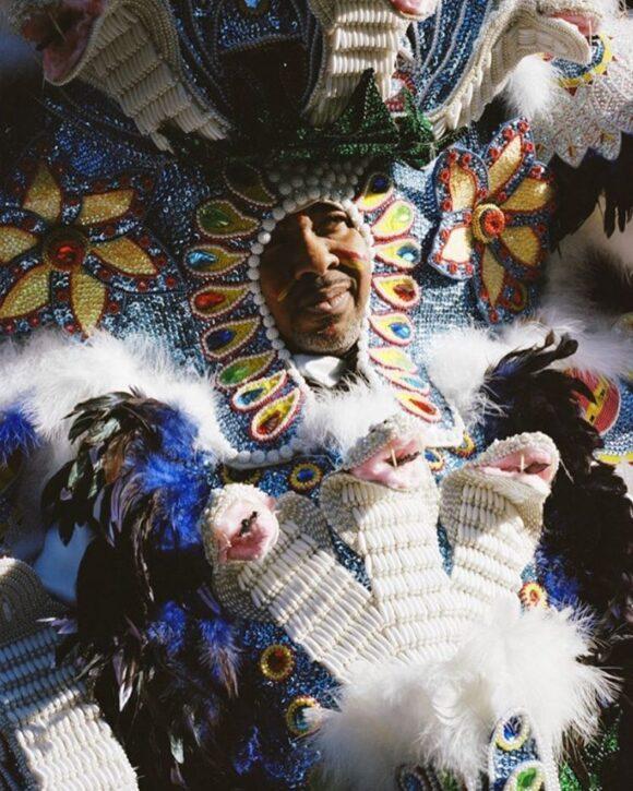 """Lors du Mardi Gras défilent """"les Indiens"""". Pour certains, l'action de porter le costume est une manière d'échapper au racisme. Pour d'autres, c'est un moyen de rendre hommage aux Amérindiens de la tribu Seminole qui ont accueillis les esclaves après leur évasion. Toutes l'année, """"Les Indiens du Mardi Gras"""" travaillent sur leur costume. Ils choisissent avec grand les plumes, les perles et les bijoux. Il leur faut une année entière et quelques milliers de dollars pour achever un costume qui peut peser jusqu'à 15 kilos."""