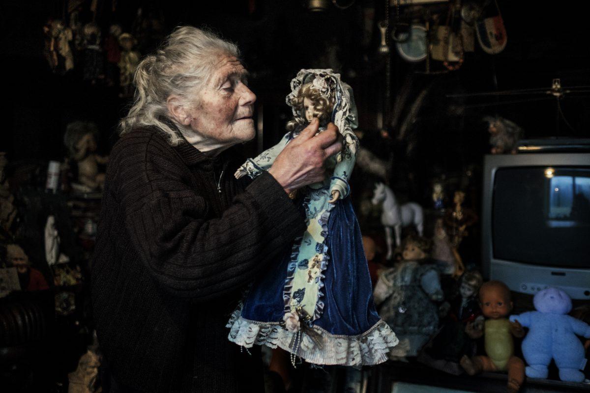 Marie-Claude joue dans son salon avec sa poupée préférée. « Elle est magnifique, n'est-ce pas ? », me dit-elle. Elle la cajole, caresse ses joues, enlève la poussière de sa robe et la remet à sa place, derrière la télé, lui ordonnant de ne pas bouger. / Extrait de « Marie-Claude, la dame aux poupées », © Mélanie Wenger