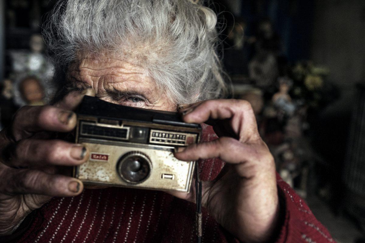 Dans le salon de Marie-Claude, au printemps. Elle a déterré un vieux Instamatic qu'elle a probablement chiné à une brocante. Il ne semble pas avoir servi récemment, malgré tout, elle invente plein d'histoires de photographies qu'elle aurait prises. / Extrait de « Marie-Claude, la dame aux poupées », © Mélanie Wenger