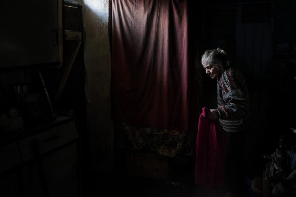 Dans la maison de Marie-Claude, à Kerberou. Marie-Claude porte trois pullovers. Le pullover du dessus, je l'ai vu s'effiler, mois après mois, jusqu'à ce que je lui en offre un nouveau. Un pullover lui dure cinq mois minimum. / Extrait de « Marie-Claude, la dame aux poupées », © Mélanie Wenger