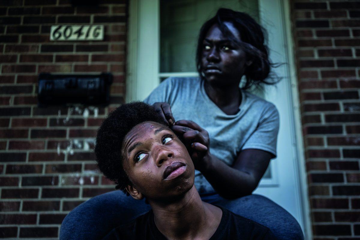 """Briana, 18 ans, tresse les cheveux de sa voisine devant sa maison, dans le nord de Flint. Claressa et sa sœur Briana sont très proches, mais pendant que Claressa se prépare pour ses seconds JO, Briana n'a pas trouvé sa voie. Elle a quitté l'école et élève son fils Bradford, que tout le monde appelle Fatdaddy. / Extrait de """"T-Rex"""","""