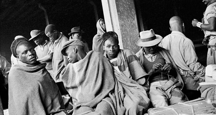 David Goldblatt Migrant mineworkers who had served their contracts on the gold mines and were waiting for a train to take them part-way to their homes in Nyassaland, (Malawi), Mayfair railway station. December 1952, January 2009