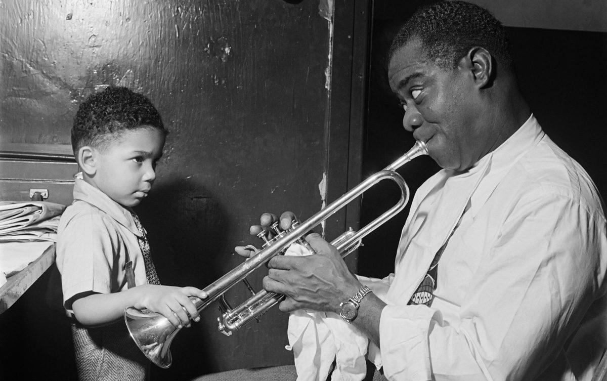 1G08V4_SCHWAB-ÉRIC-SCHWAB-Le-jazzman-américain-Louis-Armstrong-joue-pour-un-petit-garçon-dans-sa-loge,-avant-un-spectacle-en-1947-dans-un-cabaret-de-jazz-de-New-York-cropped