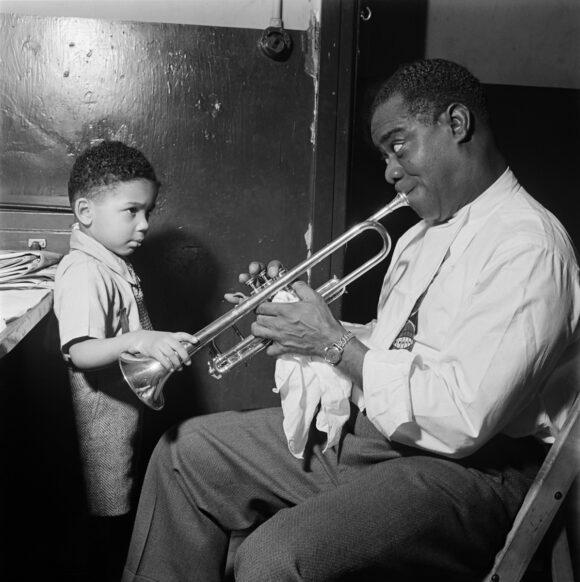 1G08V4_SCHWAB ÉRIC SCHWAB Le jazzman américain Louis Armstrong joue pour un petit garçon dans sa loge, avant un spectacle en 1947 dans un cabaret de jazz de New York