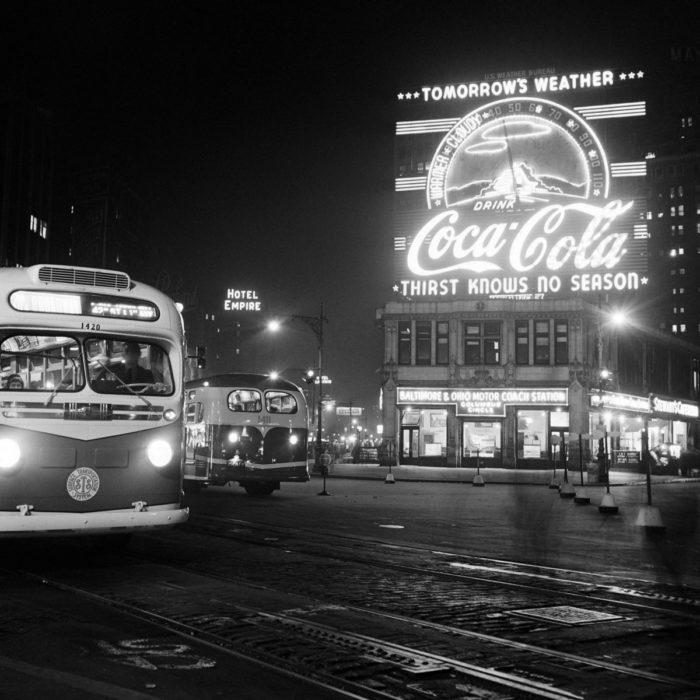 1PN8QF ÉRIC SCHWAB Des bus circulent la nuit en mars 1947 sur Columbus Circle où une publicité pour Coca-Cola annonce la météo du lendemain, à Manhattan, New York.