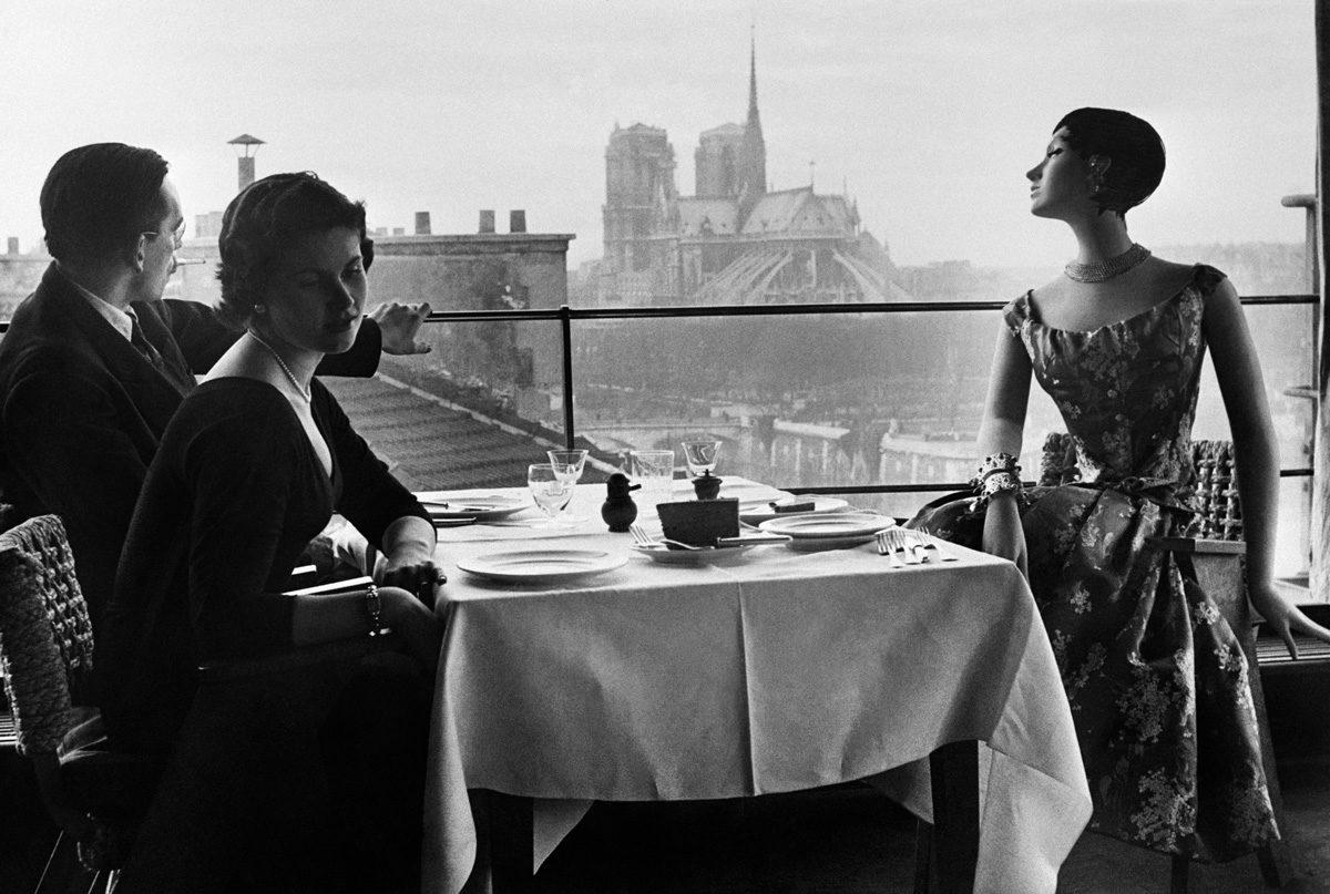 1WR888 Le mannequin Francine pose lors d'un shooting devant un modèle de cire au restaurant La Tour d'Argent, le 24 février 1955, avec vue sur la cathédrale Notre-Dame de Paris
