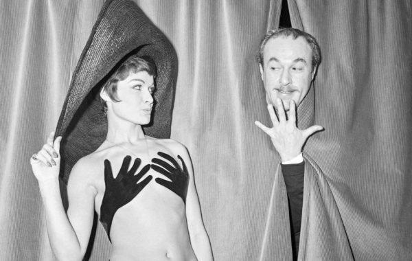 8TG2GU Le couturier français Jacques Esterel jouant sur scène lors de la présentation de son maillot de bain « Hand up » porté par son mannequin vedette Bibelot, le 13 janvier 1965 à Paris.